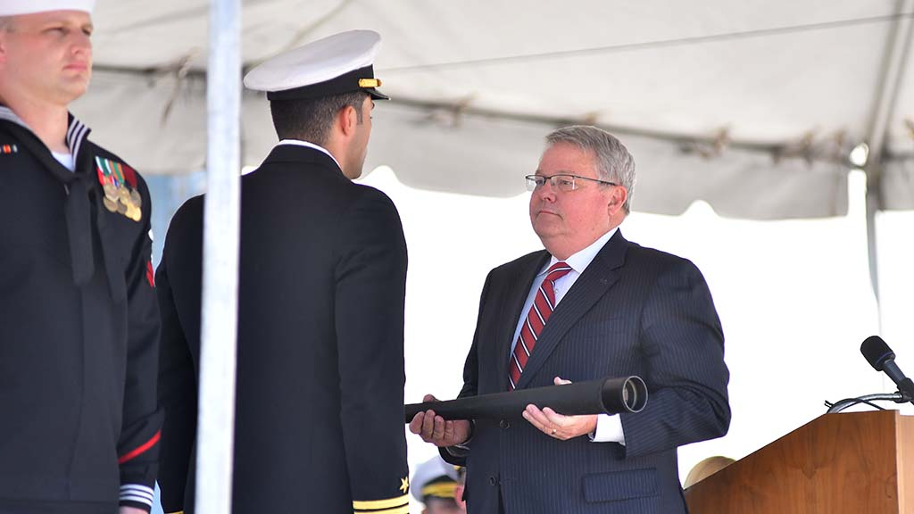 A ship officer is ready to receive the ceremonial spyglass for the USS Omaha.