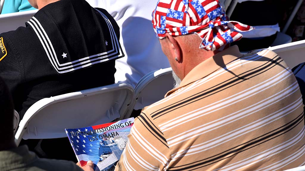 A guest at the commissioning looks at the program.