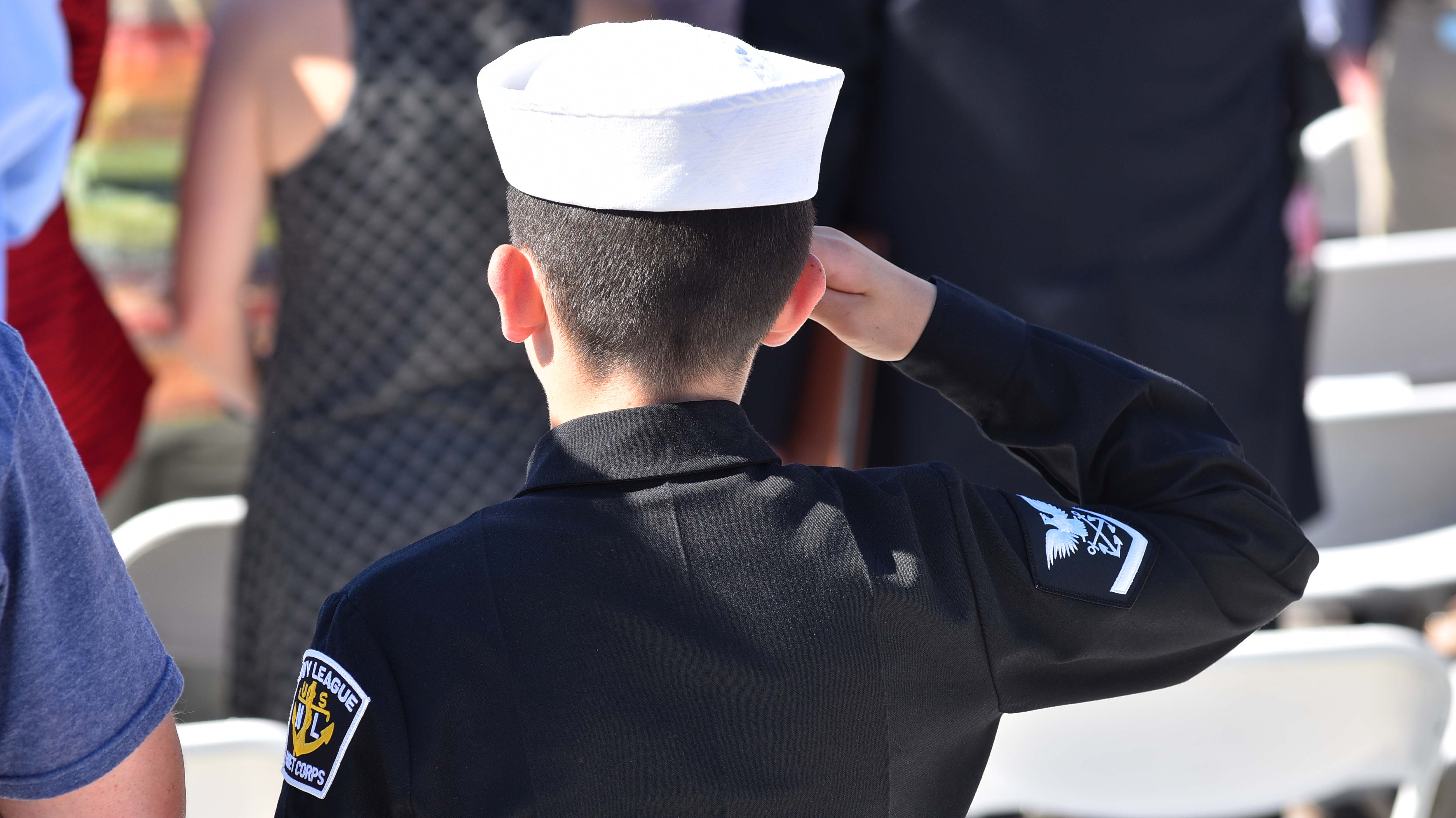 A member of the US Naval Seacadets salutes at the beginning of the program.