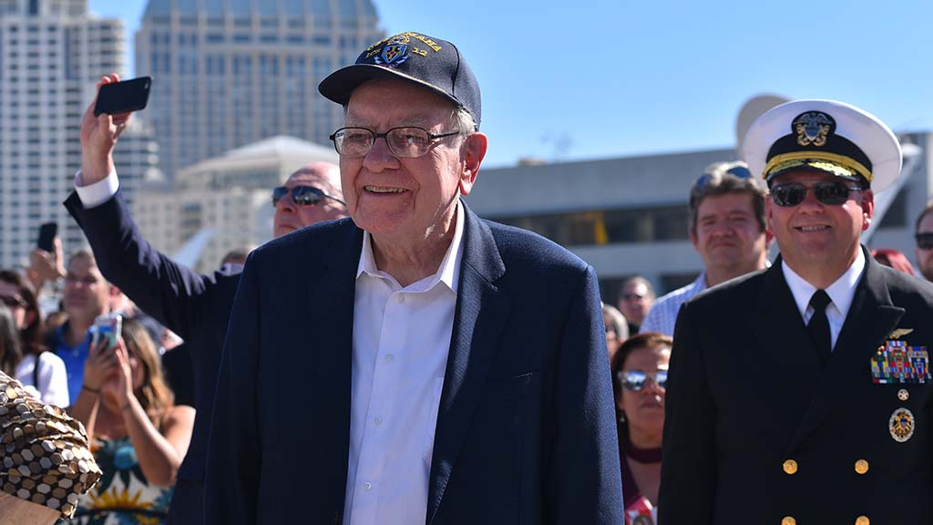 Wall Street tycoon Warren Buffet watches at crew members of the USS Omaha run onto the newly commissioned ship.