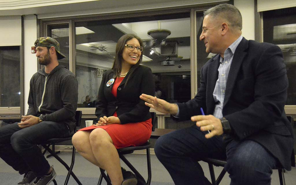 "Dulce Garcia and Tony Manolatos share a light moment at ""Grade the Media"" forum."