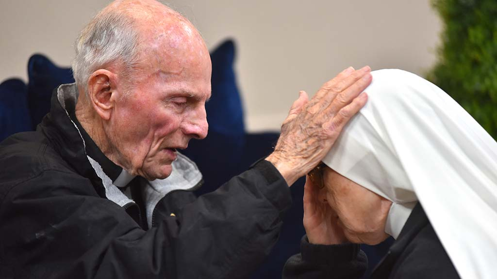 The Rev. Richard Brown blesses Sr. Soledad Hernandez after hearing her confession.