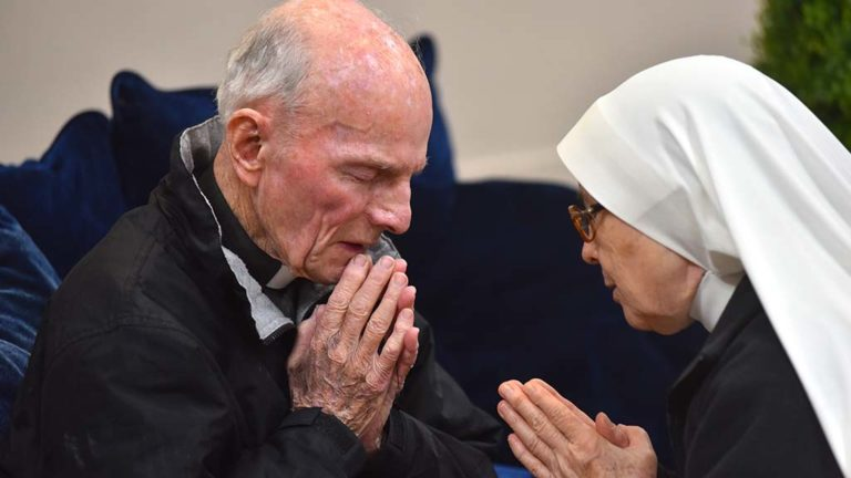 The Rev. Richard Brown prays with Sr. Soledad Hernandez after hearing her confession.