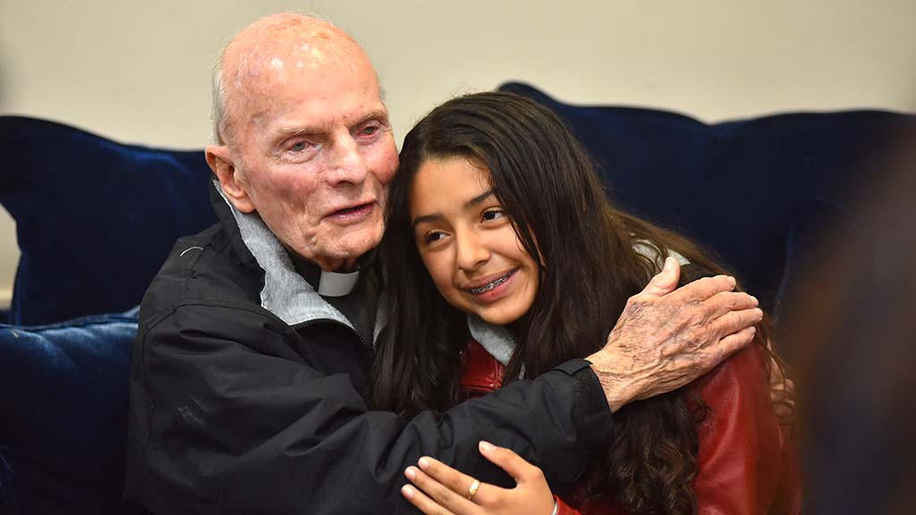 The Rev. Richard Brown hugs Anahi Balladares, 12, at the farewell dinner for him.