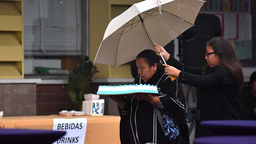 A woman brings a cake for the farewell party with some help to keep the dessert dry.