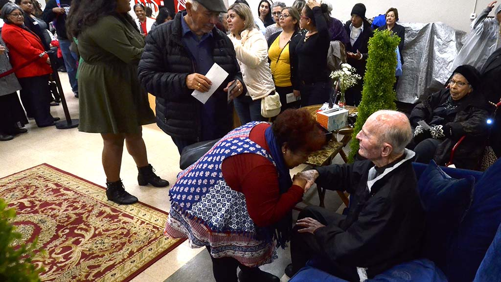 A long-time parishioner kisses Fr. Richard Brown's hand at the farewell dinner for him at Our Lady of Guadalupe Church.