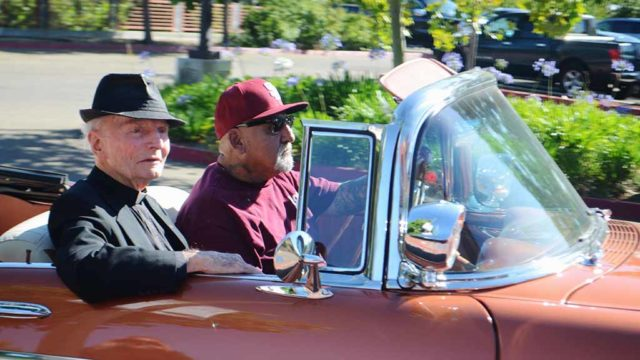 Members of the Klique Car Club in 2017 transport Father Richard Brown to his 90th birthday celebration at the Jacobs Center.