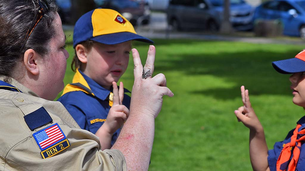 Laura Hutto (left) and Evangelina Rodgers practice the Scout salute.