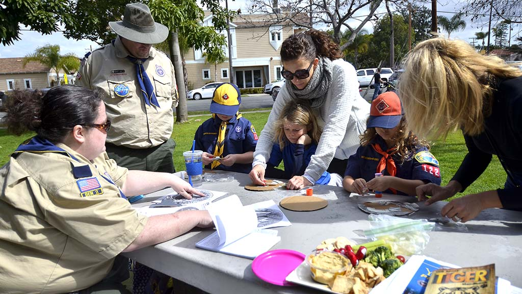 Three female Cub Scouts get help from their mothers and den leaders in Coronado. Photo by Chris Stone
