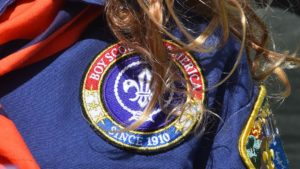 Blonde locks fall over the Boy Scouts of America patch.