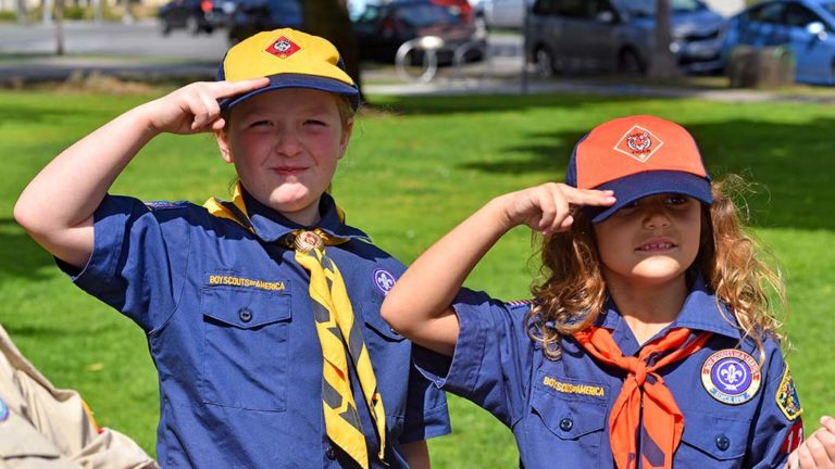 Laura Hutto (left) and Evangeline Rodgers practice their Scout salute.