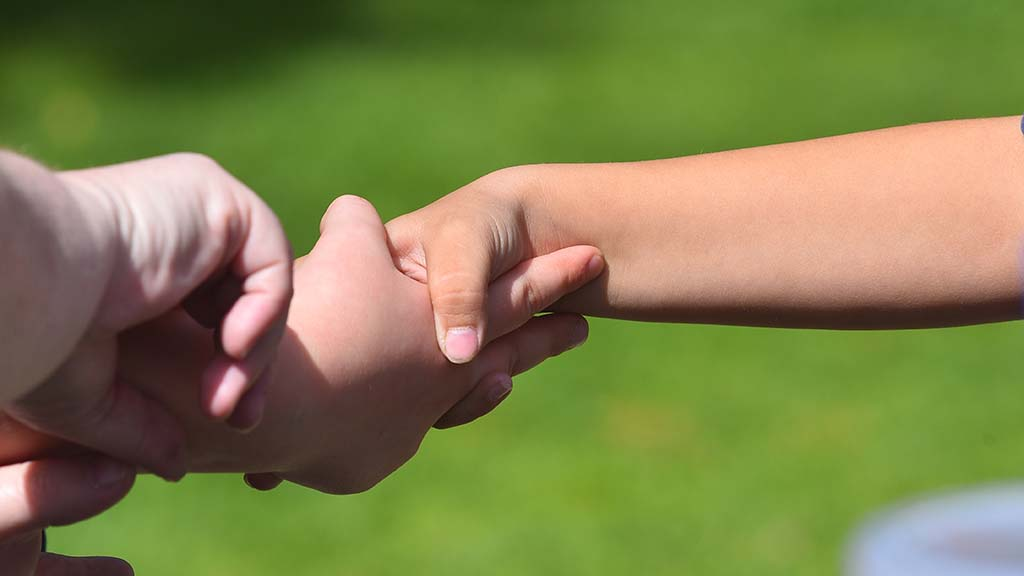 Laura Hutto (left) and Evangelina Rodgers practice the Scout handshake.