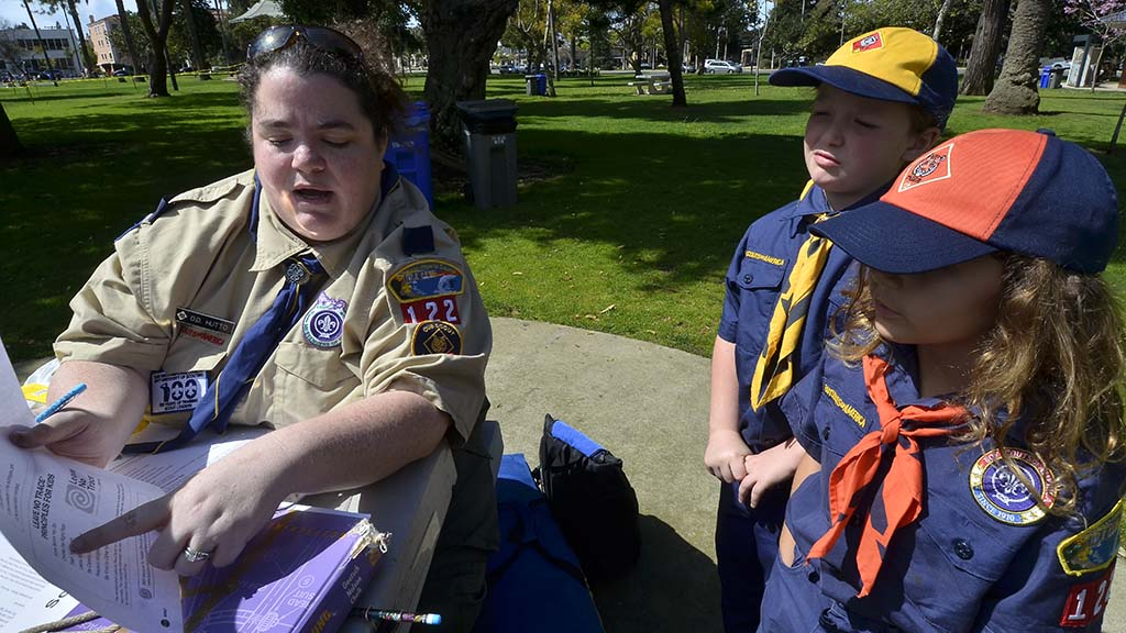 Den leader D.D. Hutto goes over the scout outdoor code with two scouts.