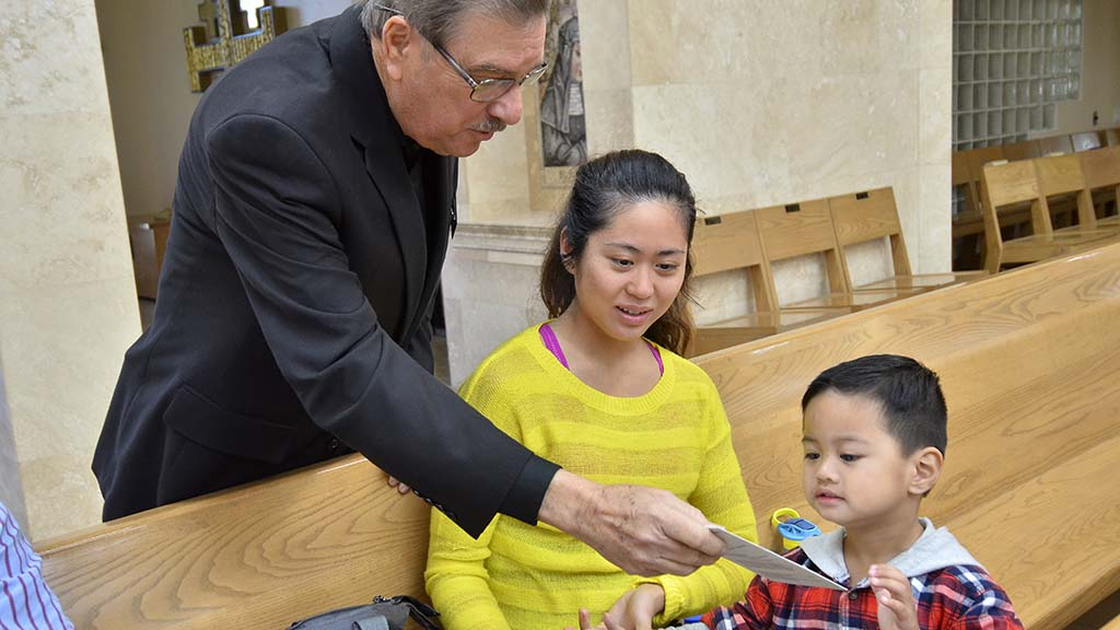 Before Mass, Blanco hands a rosary to Abbie de los Reyes and her son of Chula Vista.
