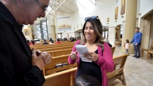 Marilee Santos, a parishioner of Corpus Christi Catholic Church, receives a rosary from Tony Blanco before Mass.