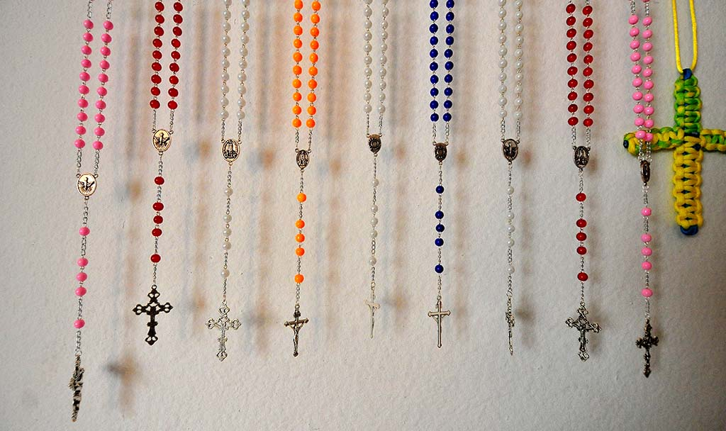 Finished rosaries are hung before being taken to his church for distribution.