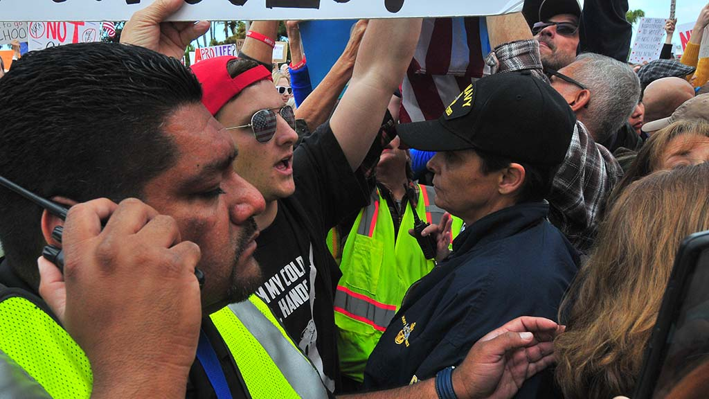A counter protestor wearing a From My Cold Dead Hands shirt is surrounded by security.