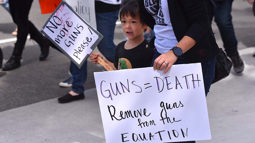A young boy and an adult protest gun violence together.