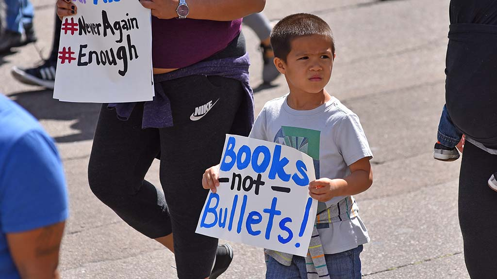 A young boy marches with adults in the protest against gun violence.