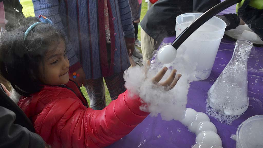 Carbon dioxide gas bubbles intrigue children at the Mad Science of San Diego booth.