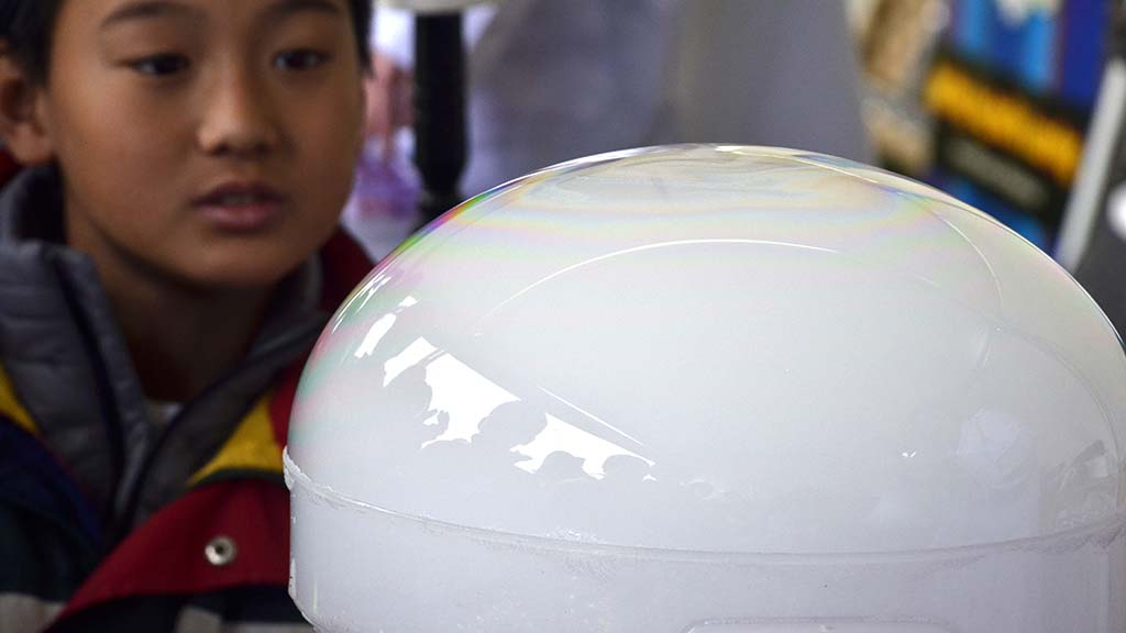 A child watches the burgeoning of carbon dioxide gas at the Festival of Science & Engineering.