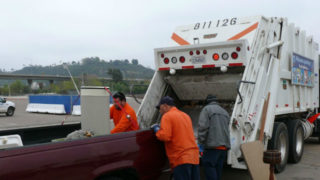 Loading bulky items into garbage truck