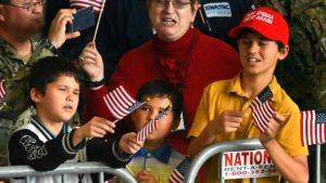 From left, Sam, Will and Wyatt Costa of Eastlake wave flags at Donald Trump talk at MCAS Miramar.