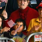 From left, brothers Sam, Will and Wyatt Costa of Eastlake wave flags at Donald Trump talk at MCAS Miramar.