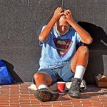 A homeless man in a Superman t-shirt sits outside of the old courthouse in downtown San Diego.