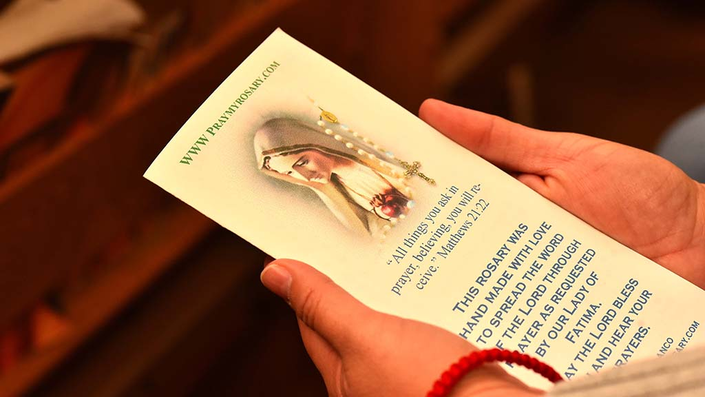 A parishioner at Corpus Christi Catholic Church looks at the pamphlet and rosary given to her by Tony Blanco.