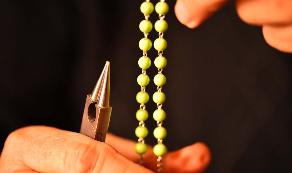 Tony Blanco uses pliers to connect beads to finish his rosary.
