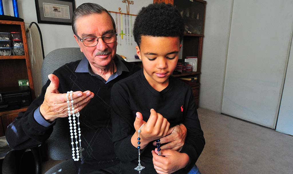 Tony Blanco and his great grandson show rosaries each made.