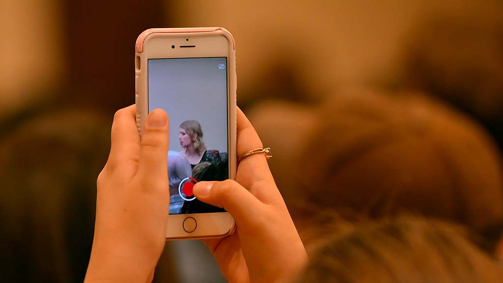 An attendee records a question and answer session with Chelsea Manning at SDSU.