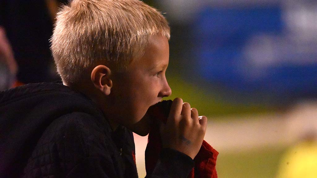 A young Legion fan holds a rally towel and watches intently.
