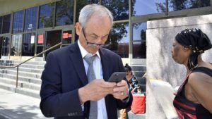 Mt. SAC attorney Sean Absher, outside the Stanley Mosk Courthouse, uses a phone after Judge Kendig's hearing.