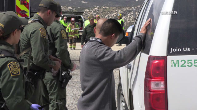 Border Patrol officers with immigrant
