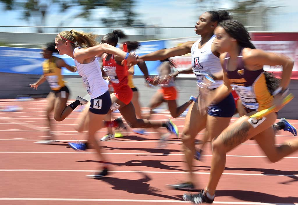 Arizona's Savaughn Christman hands off to Tatum Waggoner in a college 4x100 relay.