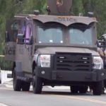 National City police officers trail armored vehicle in response to shooting.
