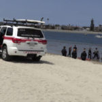 Lifeguards examine area where body was found