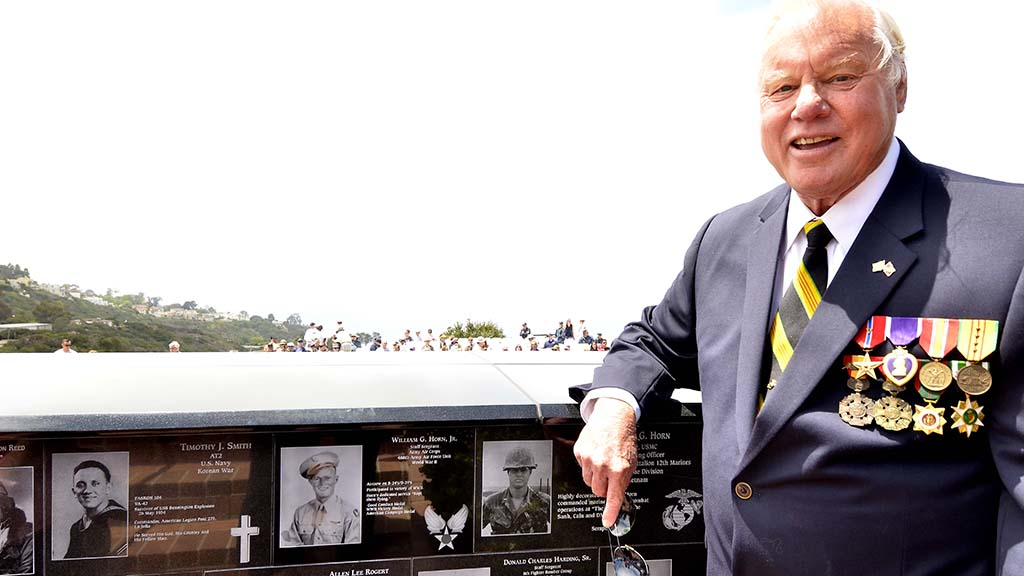 San Diego County Supervisor Bill Horn a Bronze Star Medal, and Purple Heart recipient for his service in the Marines stands by his plaque and the one of his father at Mt. Soledad National Veterans Memorial on Monday.