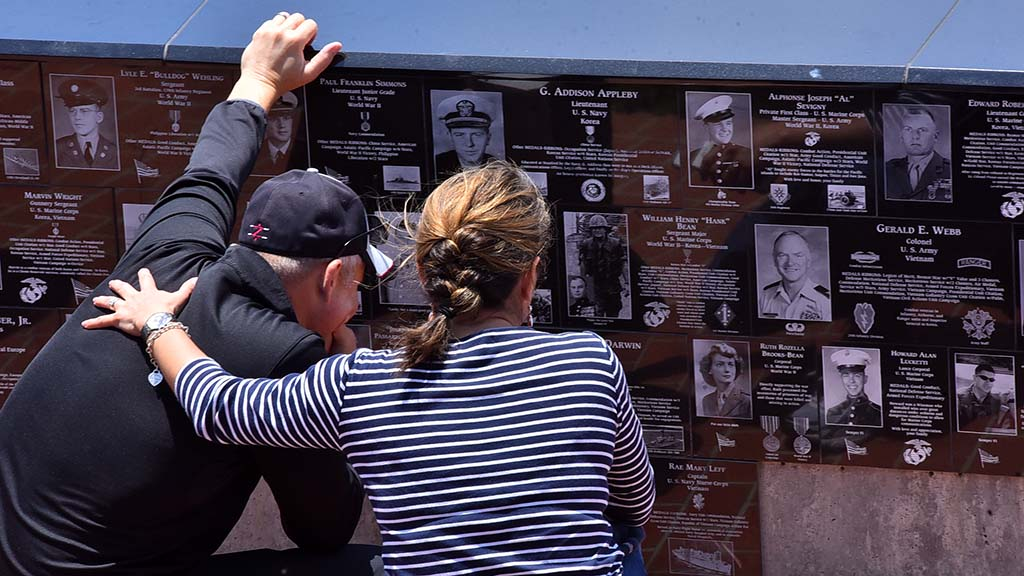 A couple reads plaques at Mt. Soledad National Veterans Memorial before the ceremony.