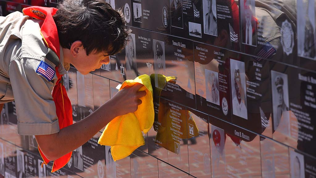 Ian Reikes, 13, of Troop 4 of the boy scouts polishes a plaque before the ceremony at Mt. Soledad National Veterans Memorial.