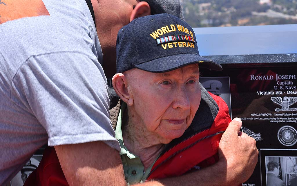 Joe Reilly, a member of the 101st Airborne Screaming Eagles, is hugged for his service at Mt. Soledad National Veterans Memorial.
