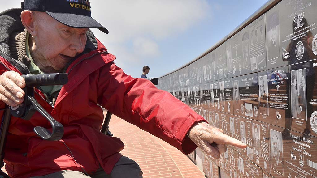 Joe Reilly, who served in the 101st Airborne Screaming Eagles, points to his plaque at Mt Soledad National Veterans Memorial.