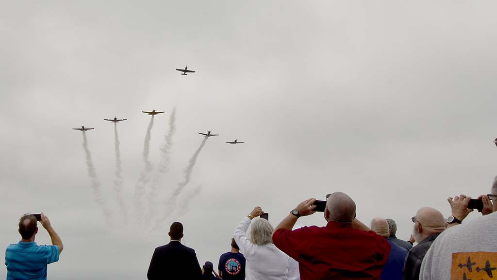 A flyover in missing man formation flies from sea over Mt. Soledad National Veterans Memorial.