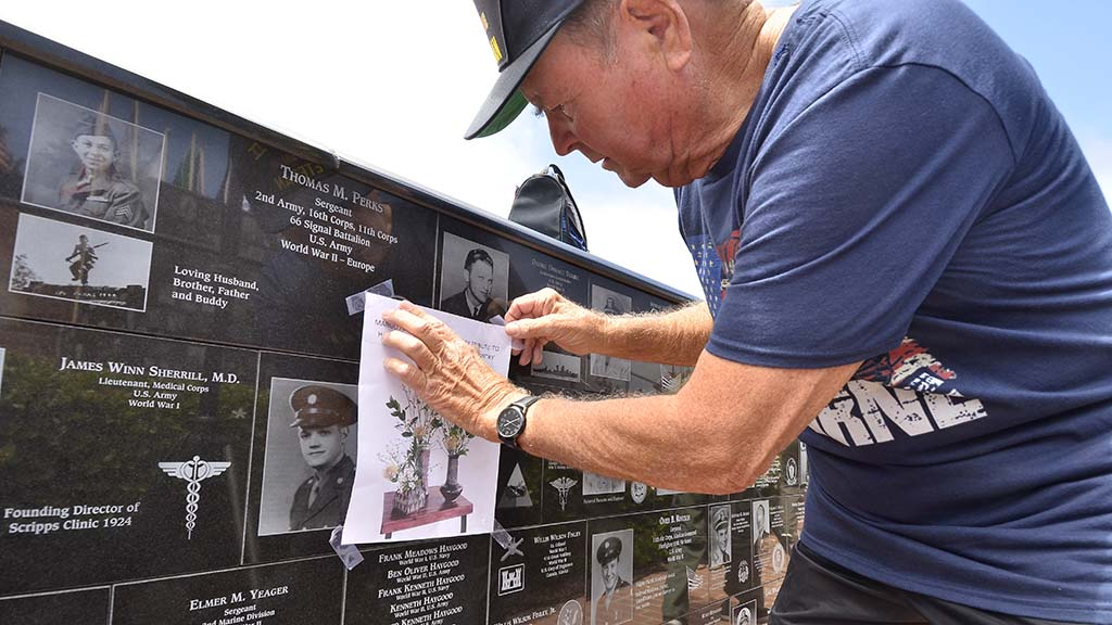 World War II veteran Kenneth Haygood attaches his daughter's illustration above his family plaque at Mt. Soledad National Veterans Memorial.