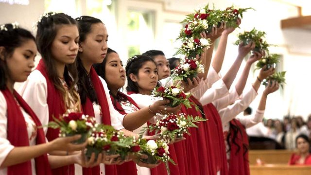 Vietnamese girls perform and scarf and flower in front of the altar.