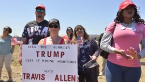 Disagreeing with President Donald Trump's endorsement for California governor, a woman holds a sign giving her support to Travis Allen.