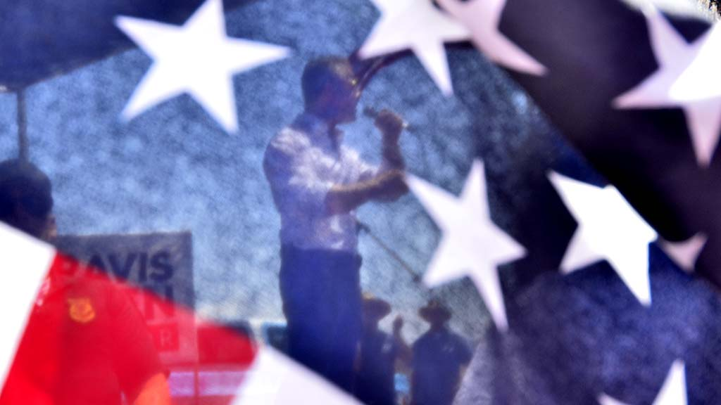 Through an American flag, Republican gubernatorial candidate Travis Allen is seen speaking.
