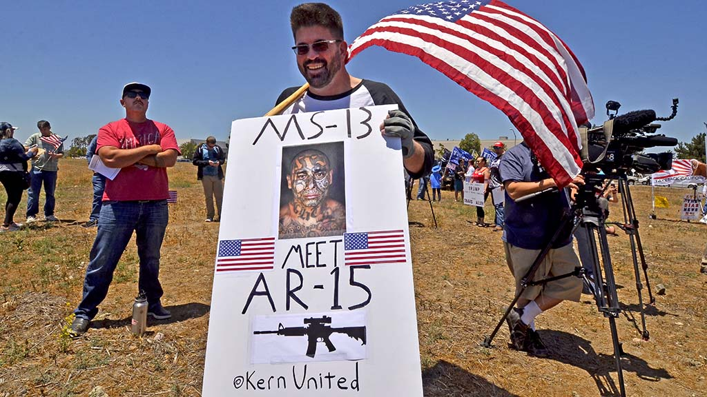 A Travis Allen supporter holds a sign about MS-13 gang members.